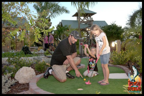 Father and son and daughter playing put put