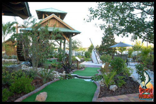Miniature golf course in with wooden building in background