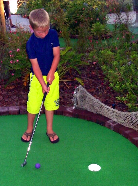 Young boy playing put put
