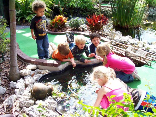 Young children playing in small pond by the course